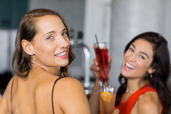 Two beautiful women holding cocktail glass. In restaurant Stock Photos
