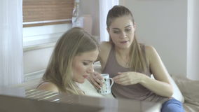 Two beautiful women at home sitting on sofa using a tablet and smiling. Two beautiful young women at home sitting on sofa or settee using a tablet PC computer stock video footage