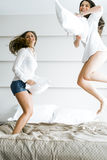 Two beautiful women jumping from joy on bed and fighting with pi Royalty Free Stock Image