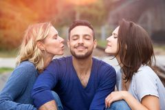 Two beautiful women kissing man on his cheeks. Two beautiful women kissing handsome men on his cheeks Stock Image