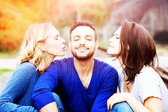 Two beautiful women kissing man on his cheeks stock image