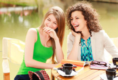 Two beautiful women laughing over a cofee. At the river side terrace - vibrat summer colors Royalty Free Stock Photography