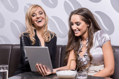Two beautiful women laughing over a coffee Royalty Free Stock Photos