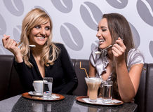Two beautiful women laughing over a coffee Royalty Free Stock Images