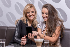 Two beautiful women laughing over a coffee Stock Photography
