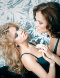 Two beautiful women in lingerie hugging on sofa Stock Photography