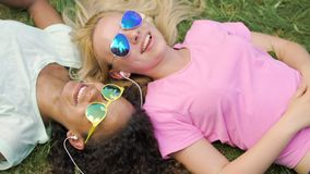 Two beautiful women listening to music in headphones and singing, lying on grass. Stock footage stock video footage