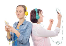 Two beautiful women listening to music with smartphone Royalty Free Stock Photography