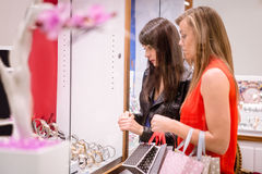 Two beautiful women looking at a display in shop Stock Image
