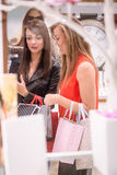 Two beautiful women looking at a display in shop Stock Photo