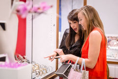 Two beautiful women looking at a display in shop Stock Photos