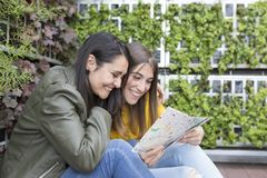 Two beautiful women looking a map. green background. They are laughing and searching for a place to stay on holidays. lifestyle. Two beautiful women looking a stock photography
