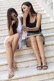 Two beautiful women looking at phone Royalty Free Stock Images
