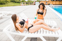 Two beautiful women are lying on chaise-longue poolside outdoors and talking. Summer time. Two beautiful women are lying on chaise-longue poolside outdoors and stock images