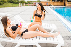 Two beautiful women are lying on chaise-longue poolside outdoors and talking. Summer time. Two beautiful women are lying on chaise-longue poolside outdoors and royalty free stock images