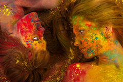 Two beautiful women lying on the floor in the colors of Holi. Closeup stock photography