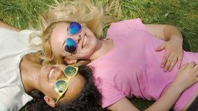 Two beautiful women lying on green lawn, talking, enjoying holidays outdoors. Stock footage stock video footage