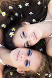 Two beautiful women lying head to head. Two beautiful brunette and blond women lying head to head with wild daisy flowers in hair Stock Photography