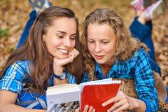 Two beautiful women lying on leaves and reading books in autumn park. Education, friendship lifestyle concept stock images