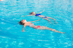 Two beautiful women lying on swimming pool water surface Stock Image