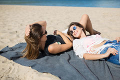 Two beautiful women lying together on beach laughing royalty free stock image