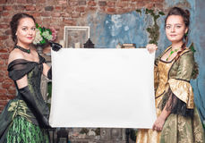 Two beautiful women in medieval dresses with empty paper Royalty Free Stock Photo