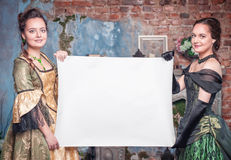 Two beautiful women in medieval dresses with empty paper Royalty Free Stock Image