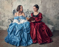 Two beautiful women in medieval dresses on the sofa reading book Royalty Free Stock Photo