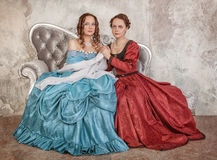 Two beautiful women in medieval dresses on the sofa Royalty Free Stock Photography