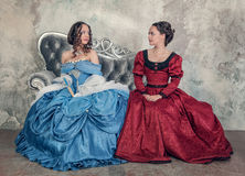 Two beautiful women in medieval dresses on the sofa Stock Photos