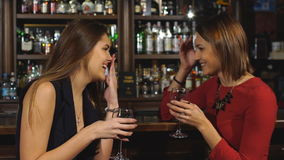 Two beautiful women met at the bar and laugh in slow motion. Two beautiful women met at the bar and talk, two beautiful woman drink at the bar stock video