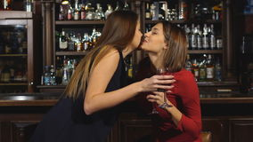 Two beautiful women met at the bar and talk. Two beautiful woman drink at the bar stock video