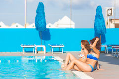 Two beautiful women next to swimming pool Stock Photography