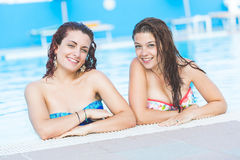 Two beautiful women next to swimming pool Royalty Free Stock Images