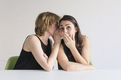 Free Two Beautiful Women Over White Background. The Blonde Girl Is Telling A Secret On The Ear To Her Brunette Friend And She Is Royalty Free Stock Photography - 156057797