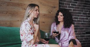 Two beautiful women in pajamas end the evening on the sofa while drinking some wine they have a great mood and happy. Faces stock footage