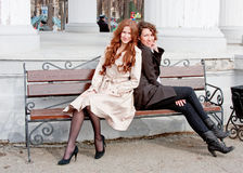 Two  beautiful women in a park sit on a bench Stock Photos