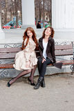 Two  beautiful women in a park sit on a bench Stock Photo