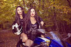 Two beautiful women passionate about motorcycles Stock Photography
