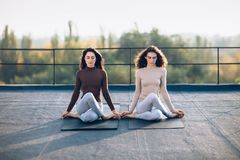 Two beautiful women perform meditative pose gomukhasana Royalty Free Stock Image