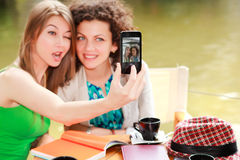 Two beautiful women photographing themselves Royalty Free Stock Photos