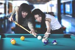 Two beautiful women playing billiard Stock Photos