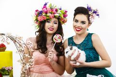 Two beautiful women playing in easter decoration with a rabbit. Stock Photo