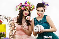 Two beautiful women playing in easter decoration with a rabbit. Royalty Free Stock Photography