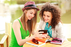 Two beautiful women playing on a smart-phone Royalty Free Stock Images