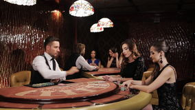 Two Beautiful Women Playing at the Table Blackjack in a Casino. Woman in Black Dress Takes the Card and Makes a Bet in a Casino, Blakjack. Elegant luxury girl in stock video footage