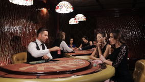 Two Beautiful Women Playing at the Table Blackjack in a Casino. Woman in Black Dress Takes the Card and Makes a Bet in a Casino, Blakjack. Elegant luxury girl in stock footage