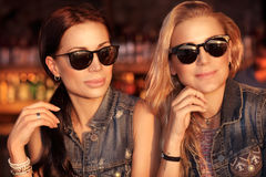 Two beautiful women. Portrait of a two gorgeous women outdoors at night, beautiful friends going out, wearing stylish jeans jackets and sunglasses over glowing Royalty Free Stock Photos