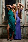 Two beautiful women posing in obsolete interior. Royalty Free Stock Photo