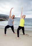 Two beautiful women practicing yoga at beach Royalty Free Stock Photo